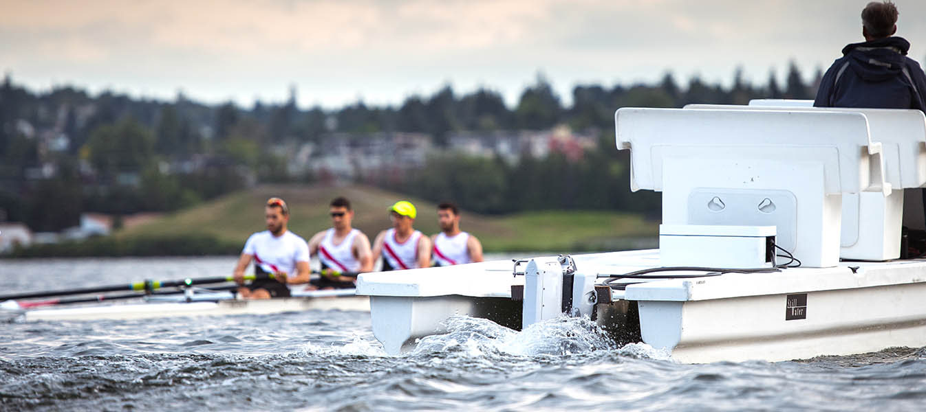 Rowers practicing and Stillwater coaching launch with electric outboard motor