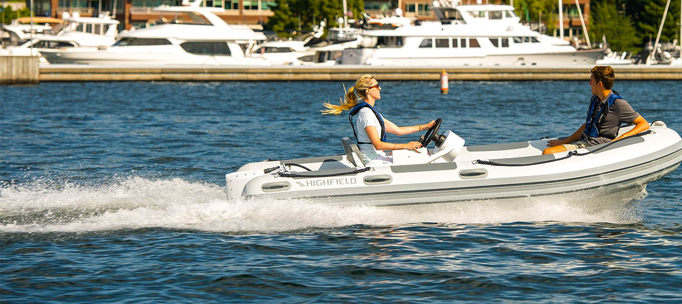 Man and woman riding fast in rigid inflatable boat with electric outbaord